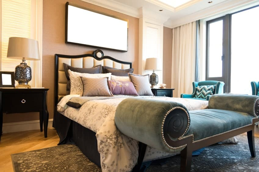 Stylish bedroom features gorgeous seats and a tufted bed over a textured area rug. It includes dark wood nightstands topped with perforated table lamps.