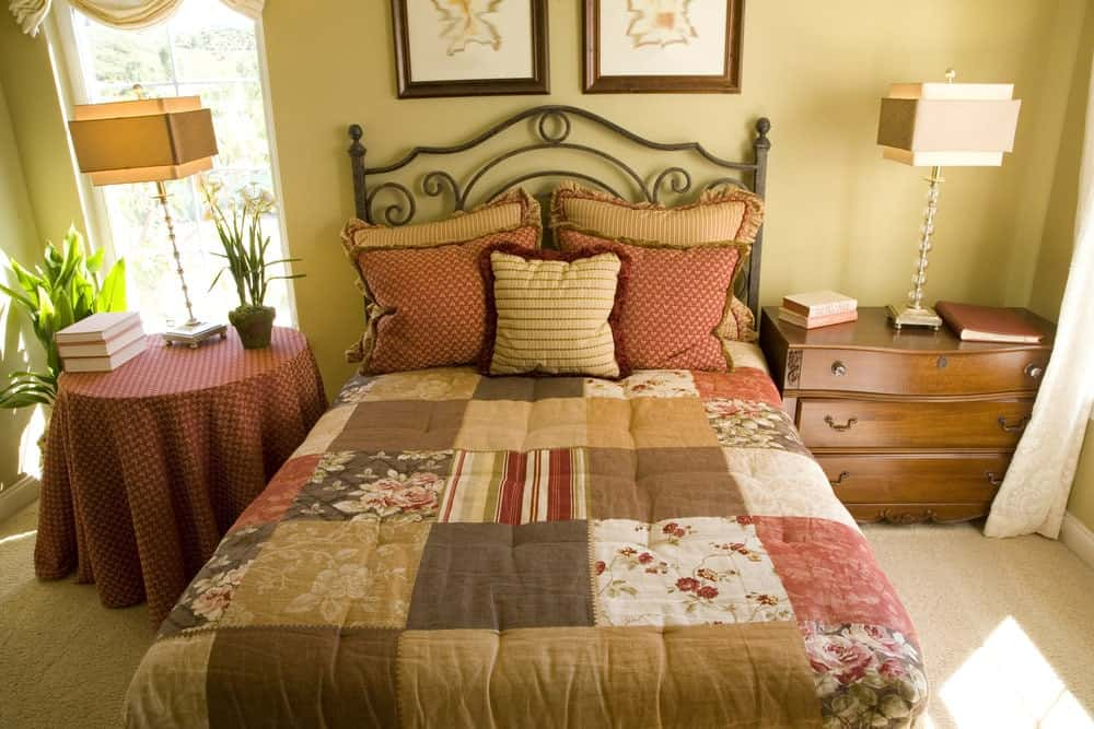 Beige bedroom with stylish table lamps and ornate metal bed dressed in checkered bedding. It has wooden and round nightstands over carpet flooring.