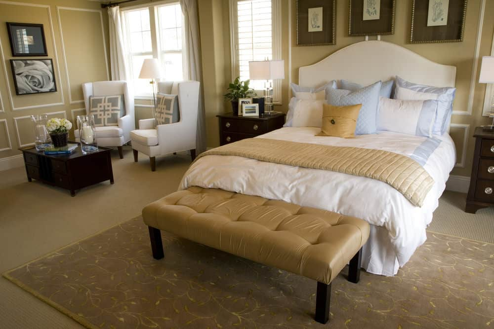 Sophisticated primary bedroom with wainscoted walls and carpet flooring topped by a patterned area rug. It includes white skirted bed and wingback chairs accompanied by a tufted bench and dark wood coffee table.