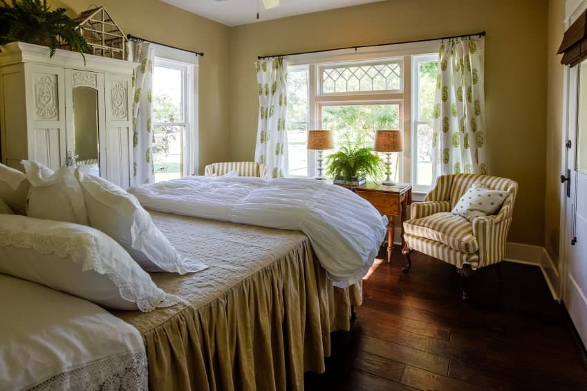 Airy bedroom offers a comfy bed and striped armchairs with a wooden console table in the middle topped by a pair of table lamps. It has wide plank flooring and glazed windows covered in flowy patterned curtains.