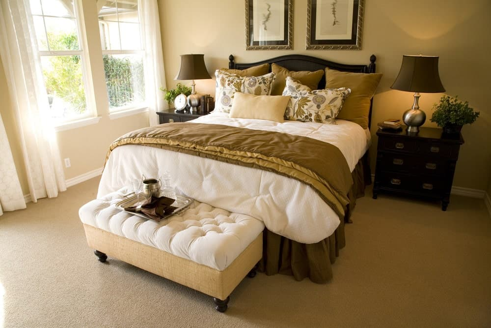 Classy bedroom boasts a tufted ottoman and a gorgeous skirted bed with framed artworks on top. It is situated in between dark wood nightstands topped with chrome table lamps.