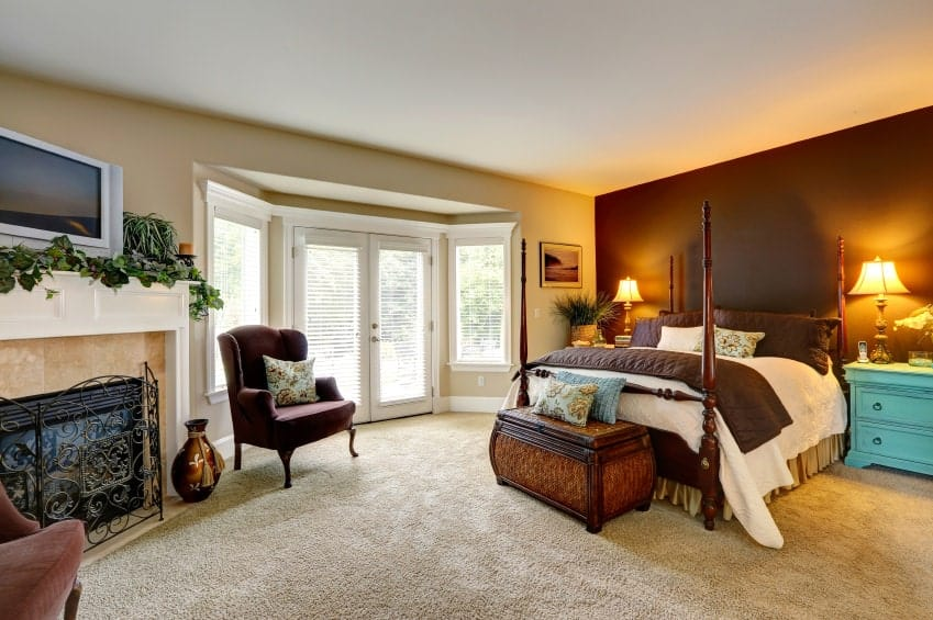 A brown accent wall adds a striking contrast in this beige bedroom offering a four poster bed and blue nightstands along with a fireplace covered with an ornate fence.