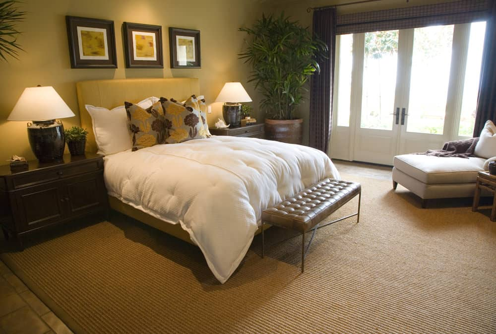 A white chaise lounge faces the upholstered bed flanked by dark wood nightstands and table lamps. It is accompanied by framed wall arts and a leather tufted bench that sits on a tan area rug.