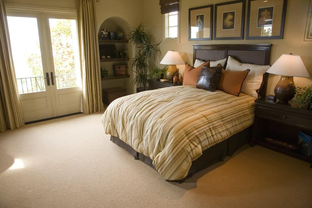 The beige bedroom features a skirted bed and an arched inset wall fitted with wooden shelving. There's a French door next to it that opens to the balcony.