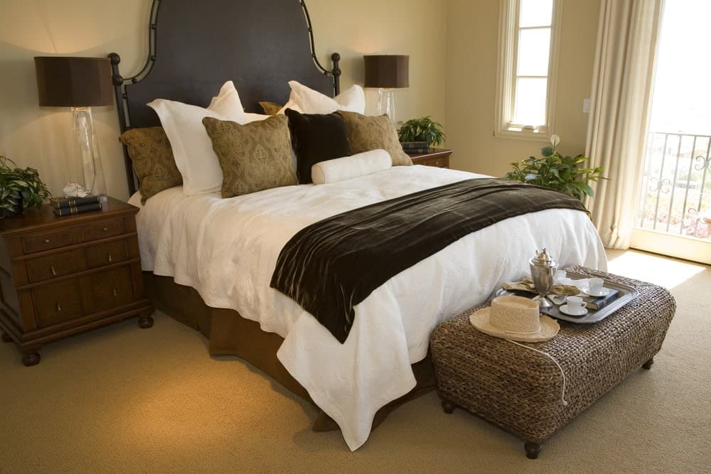 Fluffy pillows lay on the skirted bed in this beige primary bedroom with wicker ottoman and wooden nightstands topped with glass table lamps.
