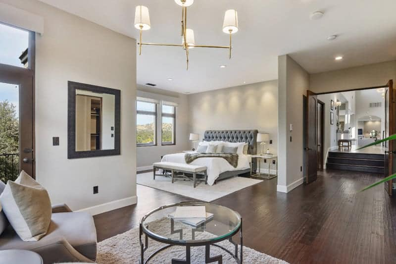The spacious primary bedroom features a gray tufted bed and a seating area illuminated by a brass chandelier. It has hardwood flooring and wooden double door leading out to the hallway.