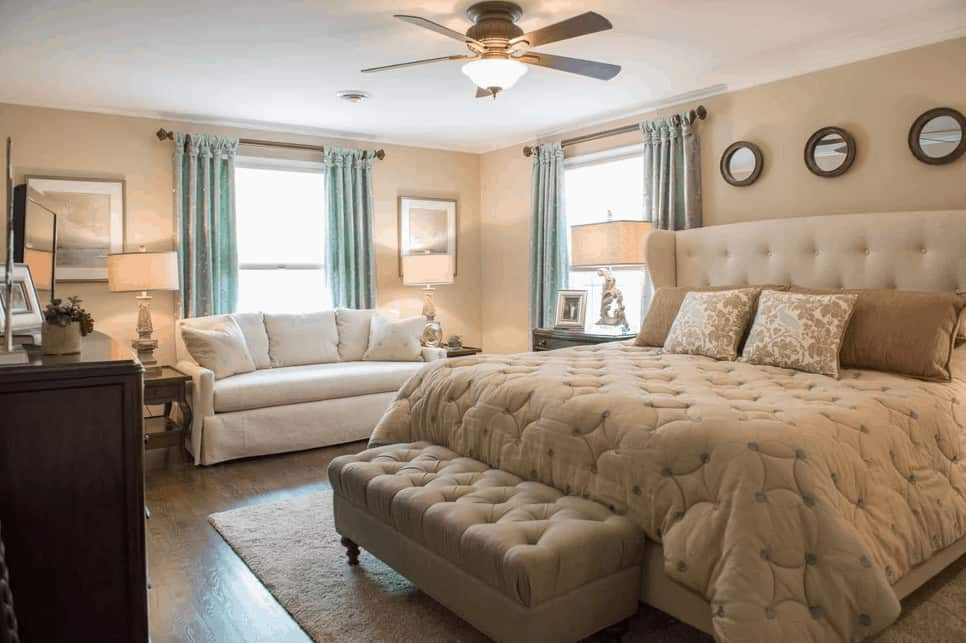 Beige primary bedroom with a skirted sofa and round wall arts that hung above the wingback bed with a tufted ottoman on its end. It has hardwood flooring and picture windows covered in charming blue draperies.
