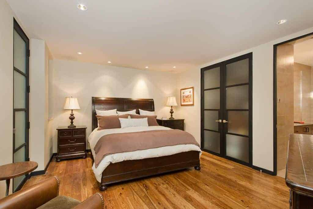 The cozy bedroom features a dark wood bed and matching nightstands over the rich hardwood flooring. It is lighted by traditional table lamps and recessed ceiling lights.