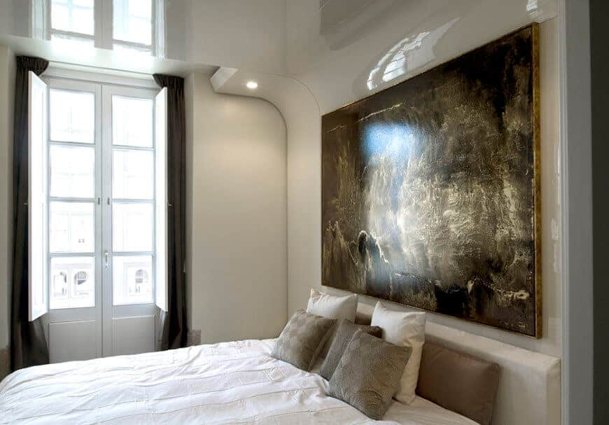 Natural light streams in through the glazed window in this primary bedroom with a cozy bed and interesting artwork mounted on the beige high gloss wall.