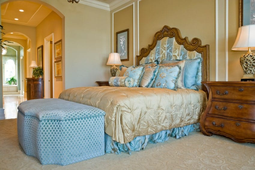 A gorgeous skirted bed with a stylish blue ottoman on its end is the highlight in this primary bedroom with textured carpet flooring and beige wainscoted walls mounted with framed artworks.