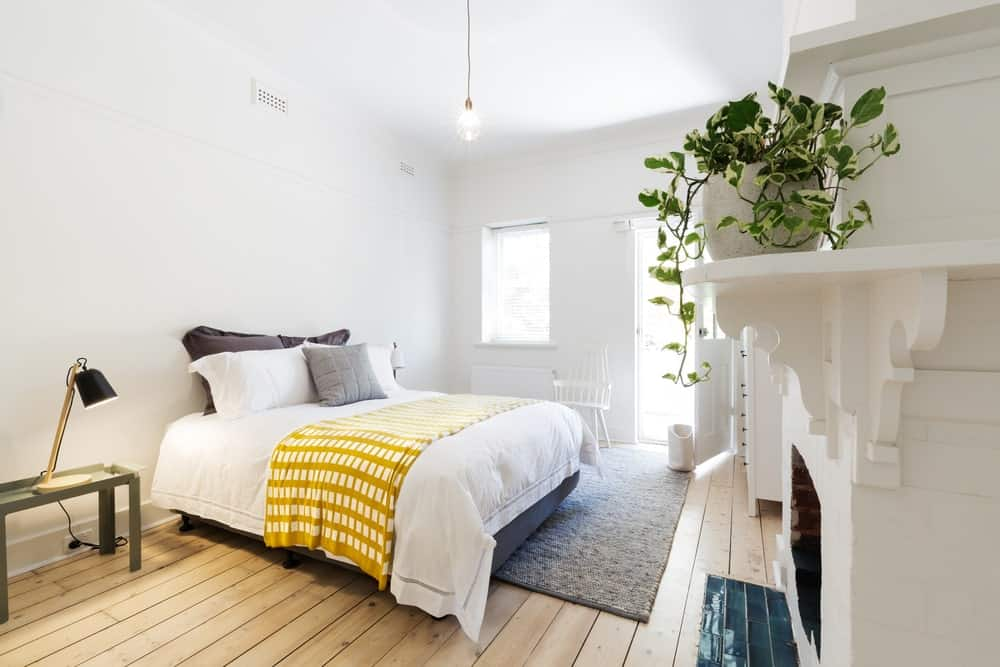 The traditional bed of this Scandinavian-style bedroom has a fireplace to prevent chilly toes. This fireplace is inlaid with white concrete and wood forming a shelf above accented with potted plants. These are all complemented by a beautiful hardwood flooring.