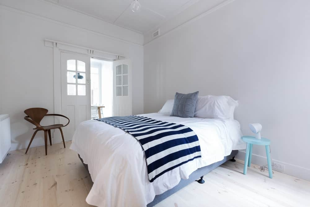 This bedroom gives you a bright morning awakening with with its white walls, white ceiling, white bed sheets and a light hardwood flooring. These complemented by the striped bed scarf, light blue bedside table and a dark brown wooden chair.