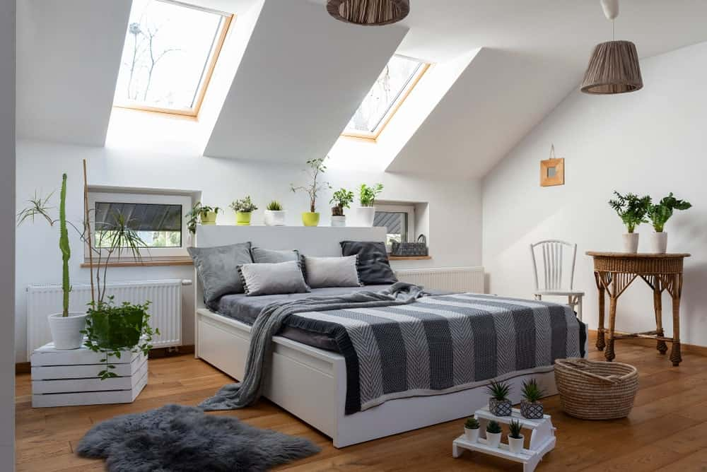 This Scandinavian-style bedroom has a white shed ceiling that has a pair of skylights bearing natural light down onto the bed that has a white frame and gray sheets. This stands out against the hardwood flooring matching with the small wooden table and the basket hoods of the pendant lights.