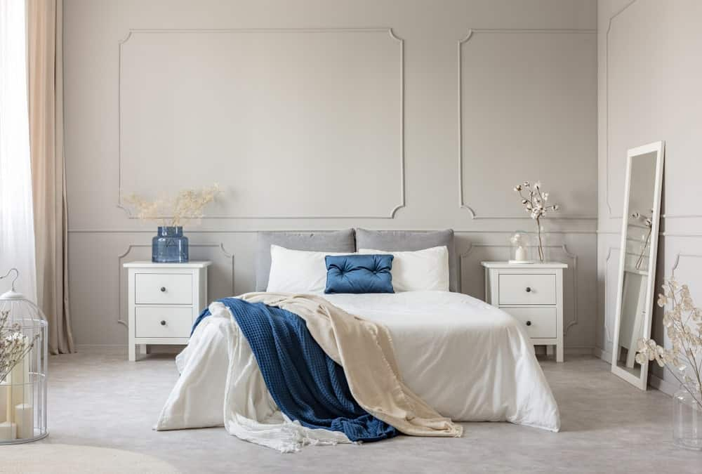 The light gray walls of this Scandinavian-style bedroom has an elegant finish that complements the white wooden bedside tables flanking the traditional bed with white sheets that make the blue pillow and blanket stand out.