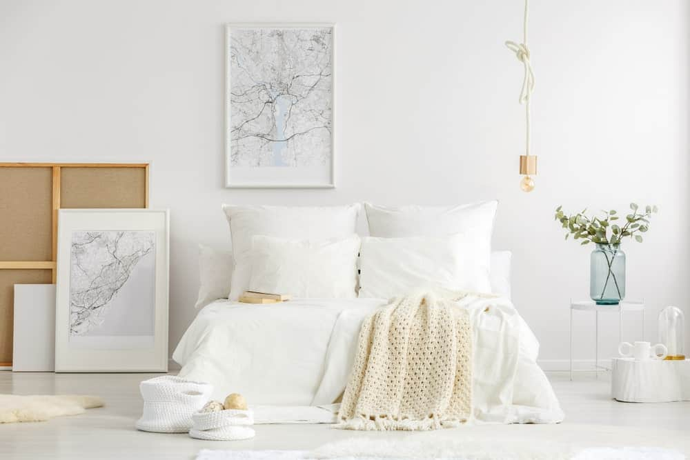This Scandinavian-style bedroom embraces the white and brightness of the walls and flooring with a platform bed that has white sheets and pillows. This is paired with a small white bedside table and a couple of framed artworks.