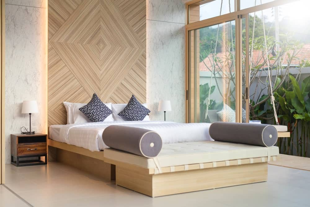 There is a large glass wall with sliding glass doors on the side of the wooden bed. This glass wall features a lush green landscape outside that provides the green contrast for the bare wood elements of the bed, its headboard and the lounger bench at the foot of the bed.
