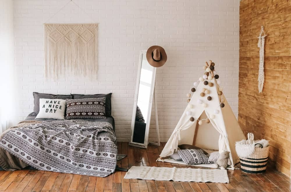 This is a boy's bedroom in a charming Scandinavian-style. It has a simple hardwood flooring that complements the two different walls. One is made of white bricks and the other has a brown wooden hue. This goes well with the gray bed and the teepee canvas hut beside it.