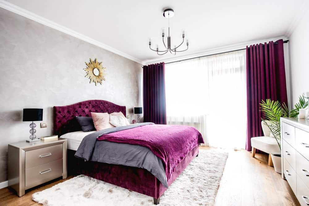 The highlight of this Scandinavian-style bedroom is the brilliant purple velvet bed. It stands out against the light gray walls and white ceiling. It also matches with the thick curtains of the large glass window that brighten up the light hardwood flooring.