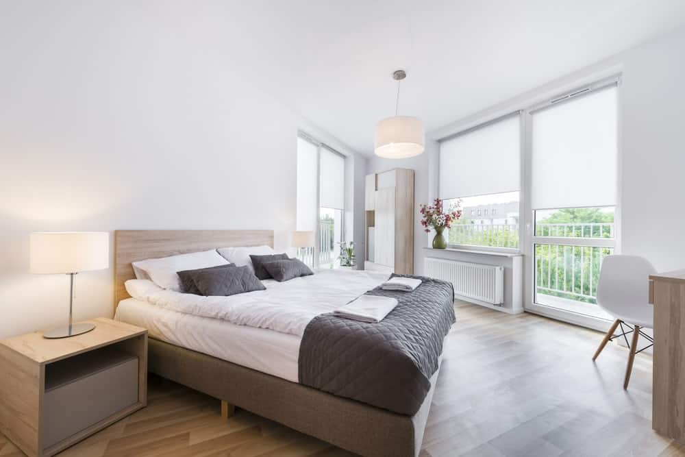 The brightness of this Scandinavian-style bedroom is due to the white walls and ceiling that are brightened by the natural lights coming in from the glass windows and glass door. This is augmented by the pendant light that matches with the two table top lamps on simple wooden bedside tables.
