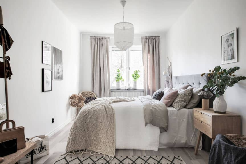 The comfortable and inviting traditional bed has a gray tufted headboard that complements the white wall. This headboard has a wooden bedside drawer beside it bearing a modern lamp and a potted plant.