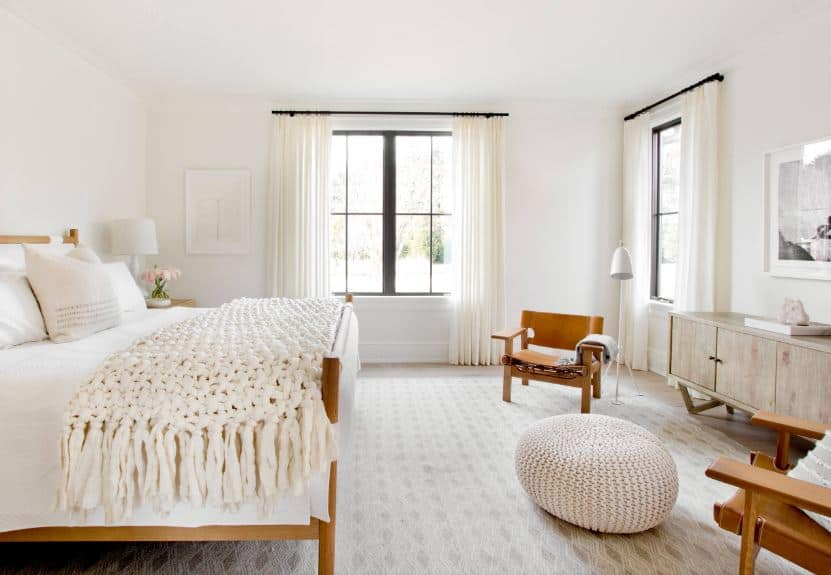 The wooden bed frame that is paired with a white cushion and sheet matches well with the pair of wooden armchairs at the sitting are by the foot of the bed. The sheets of the bed are as white as the walls and ceiling brightened by the windows.