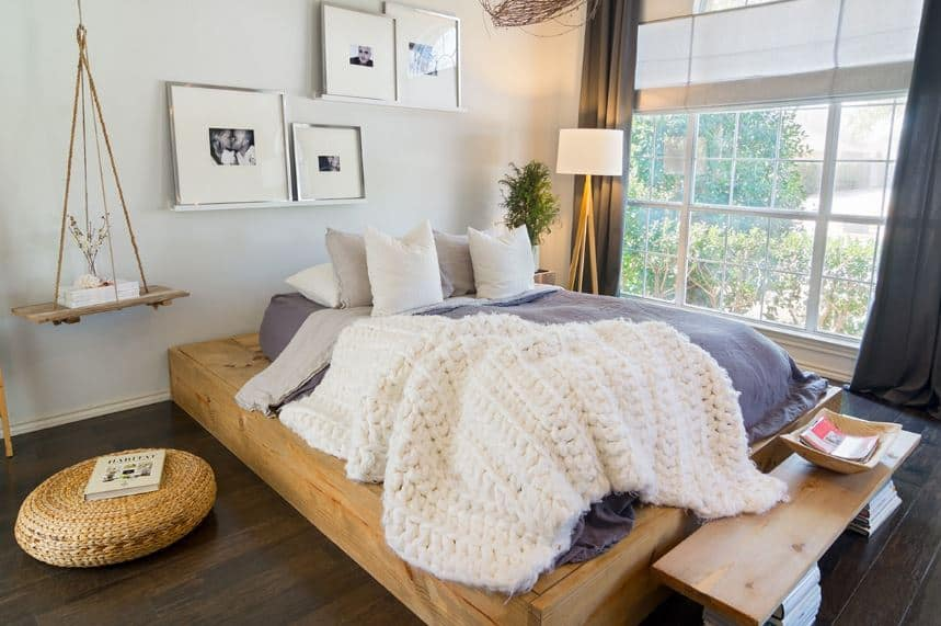 This charming bedroom has a wooden platform with a light hue contrasting the dark hardwood flooring. This wooden platform is topped with a bed cushion that has gray sheets matching the curtains of the large window.