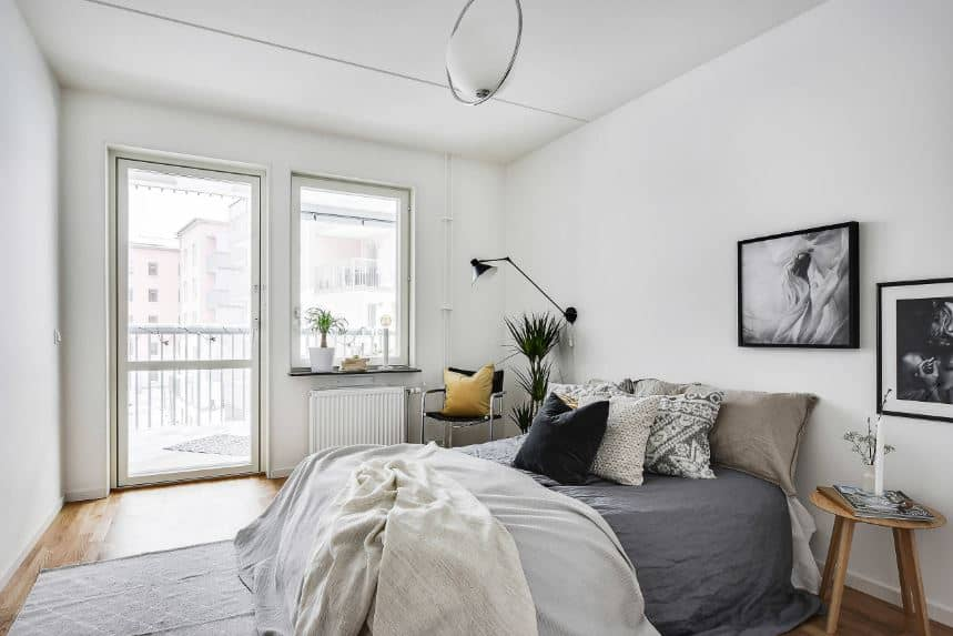 The glass window and the door beside it brings in an abundance of natural lighting that brightens up the white walls and ceiling. These bright elements are somewhat subdued by the gray sheets of the bed and the black and white framed artworks.