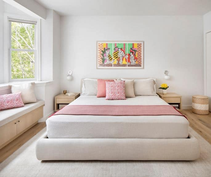 The light gray bed and its matching light gray sheets blend with the light gray area rug. These provides a nice and simple background for the colorful stand-out elements of the bed scarf, wall-mounted painting and the pillows of the bed and sitting area by the window.