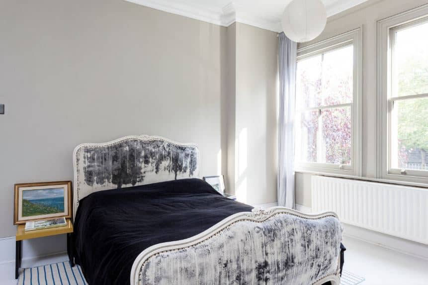 The traditional bed has a distressed chic quality to it that is paired with a black bed sheet that stands out against the light gray walls and white ceiling that hangs a spherical pendant light by the pair of windows that has the heater underneath.