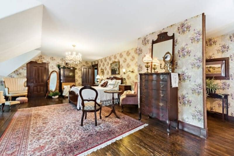 The lovely hardwood flooring is accented with a pink patterned area rug that extends from the sitting area to the wooden sleigh bed with white sheets and a wooden headboard that stands out against the beige floral wallpaper and white ceiling that has a brilliant chandelier.