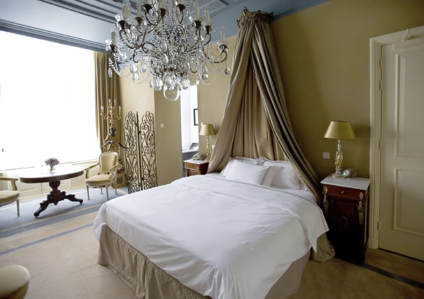 The decorative light brown curtain by the head of the bed matches with the side skirting of the traditional bed that is flanked by two elegant bedside cabinets with white table tops bearing table lamps with a golden hue. These are all contrasted by a gray tray ceiling bearing a brilliant crystal chandelier.