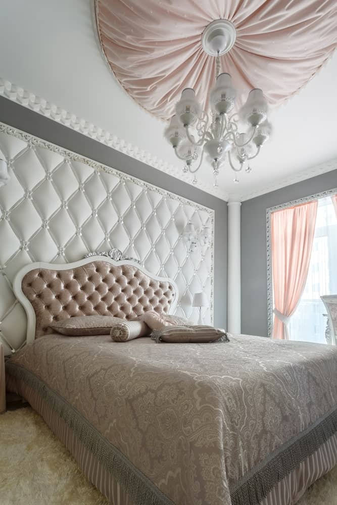 This is a bright and airy Victorian-style primary bedroom that has a traditional bed paired with an elegant tufted headboard of brown velvet cushion. This matches the tufted wall panel behind the headboard that pairs well with the white ceiling that has a white chandelier in the middle.