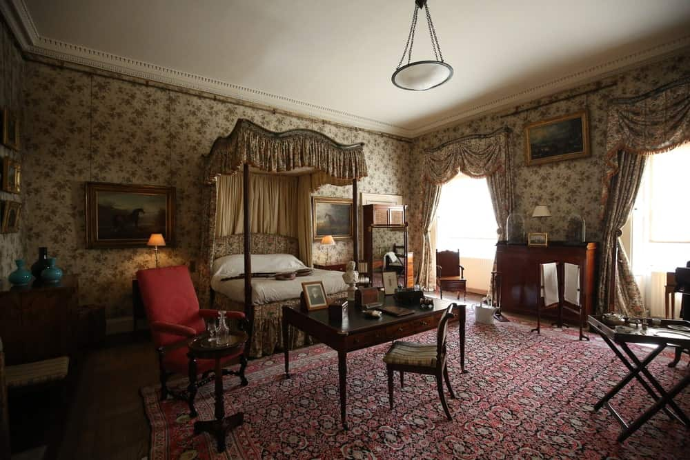 Victorian style primary bedroom with crown molding, interior wallpaper, framed photos on the wall, a four-poster bed, and seating areas on a large area rug.