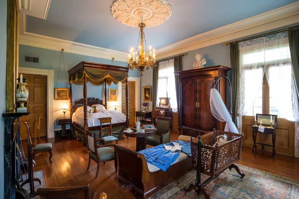 This Victorian-style bedroom is dominated by the dark brown hues of the four-poster bed that matches with the rest of the various furniture that almost crowds in the room. This is contrasted by the blue walls and ceiling that has a lovely chandelier hanging over the sitting area.