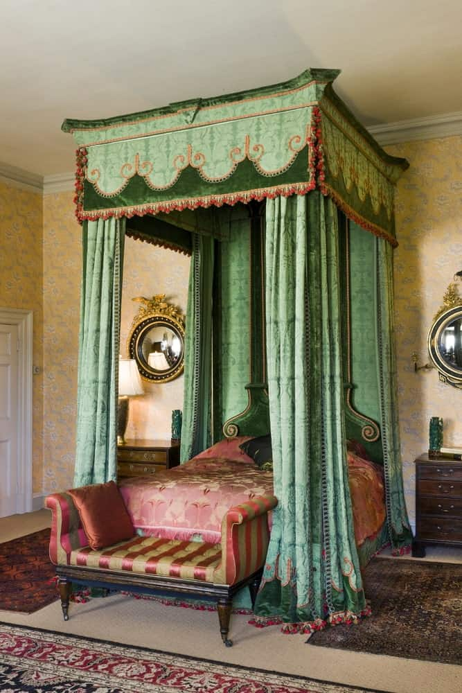 This is a colorful Victorian-style bedroom with various elegant patterns. The four-poster bed has red patterned sheets that stand out against its green patterned curtains. These curtains stand out against the yellow patterned walls with floral patterns.