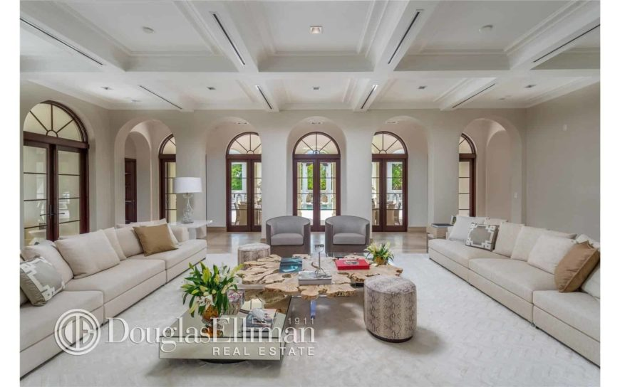 Huge living space featuring a pair of long couches and stylish center tables with ottomans on the side, set on the area's beautiful carpet flooring.