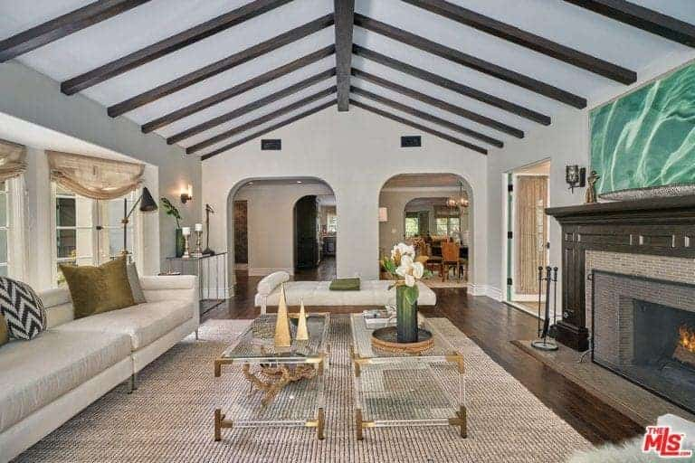 Mediterranean living room with a vaulted ceiling with beams and hardwood flooring. The area features a long white couch with two glass center tables along with a large fireplace.