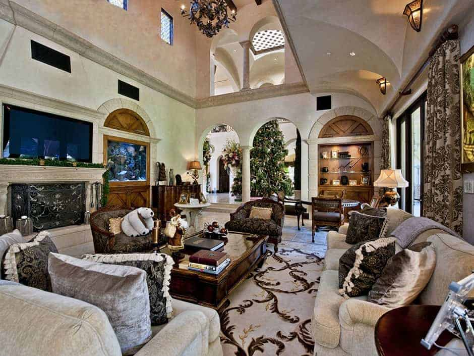 Mediterranean family living room boasting elegant seats and a classy center table lighted by wall lights and a gorgeous chandelier hanging from the two-storey ceiling. The room also has a large fireplace and a widescreen TV just above it.