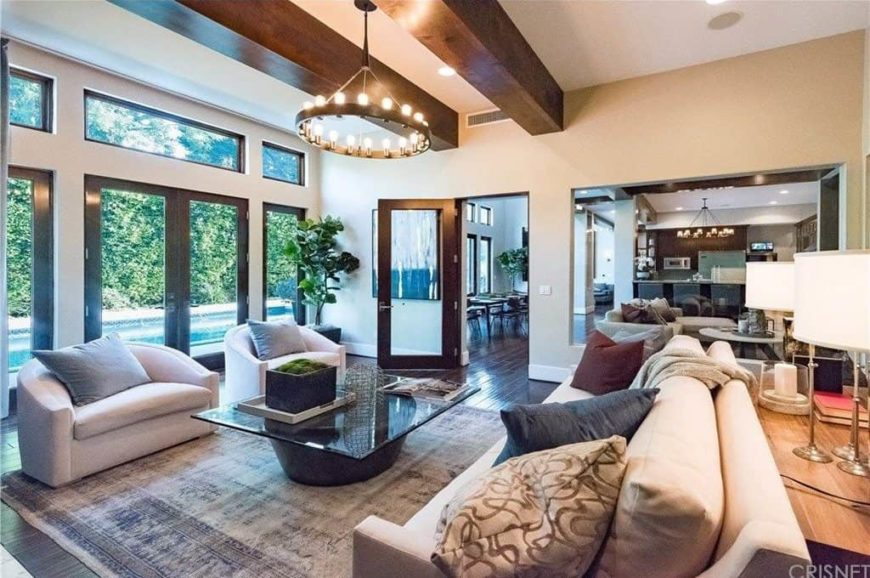 A gorgeous living room setup with elegant seats and a glass top center table lighted by a fancy ceiling light hanging from the ceiling with large beams.