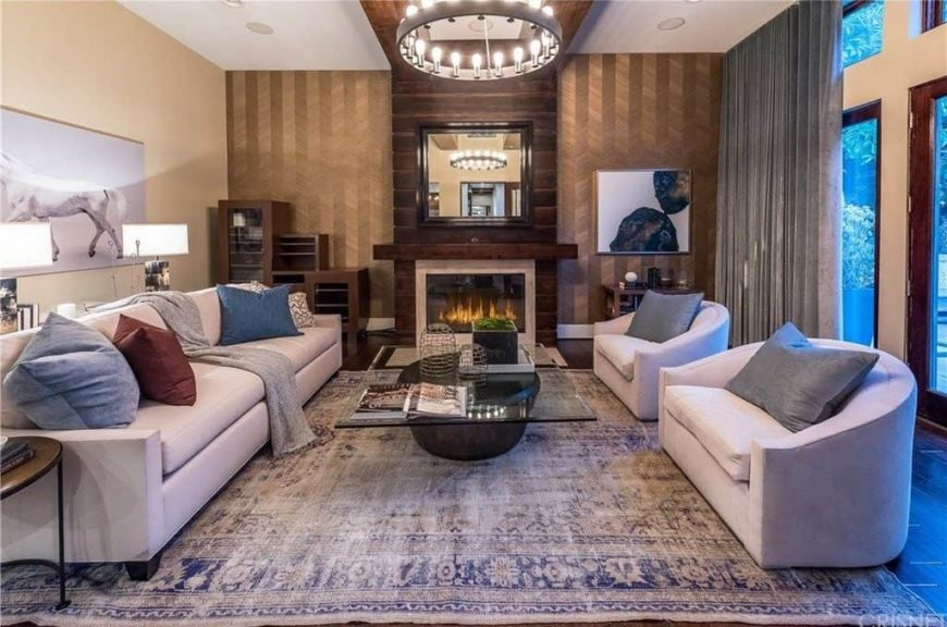 Elegant formal living room with a long couch and a couple of chairs along with a glass top center table and a fireplace.