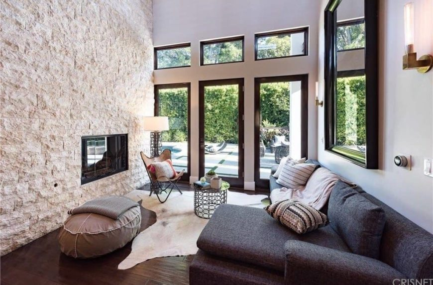 Large living room boasting a stone wall with a fireplace, along with a black L-shape sofa set under the room's tall ceiling.