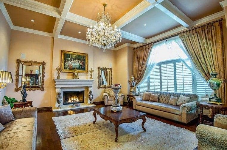 A luxurious-looking living room boasting a beautiful coffered ceiling and a glamorous chandelier. The room also has a set of elegant furniture along with gorgeous window curtains.