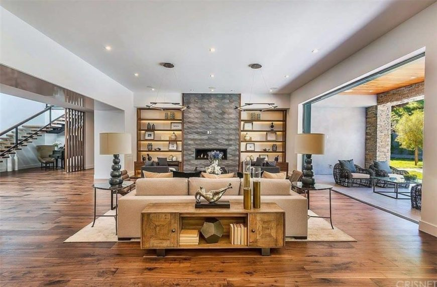 Large formal living room featuring hardwood flooring and a white ceiling. The area has a set of elegant furniture along with a modern fireplace with built-in shelving on both sides.
