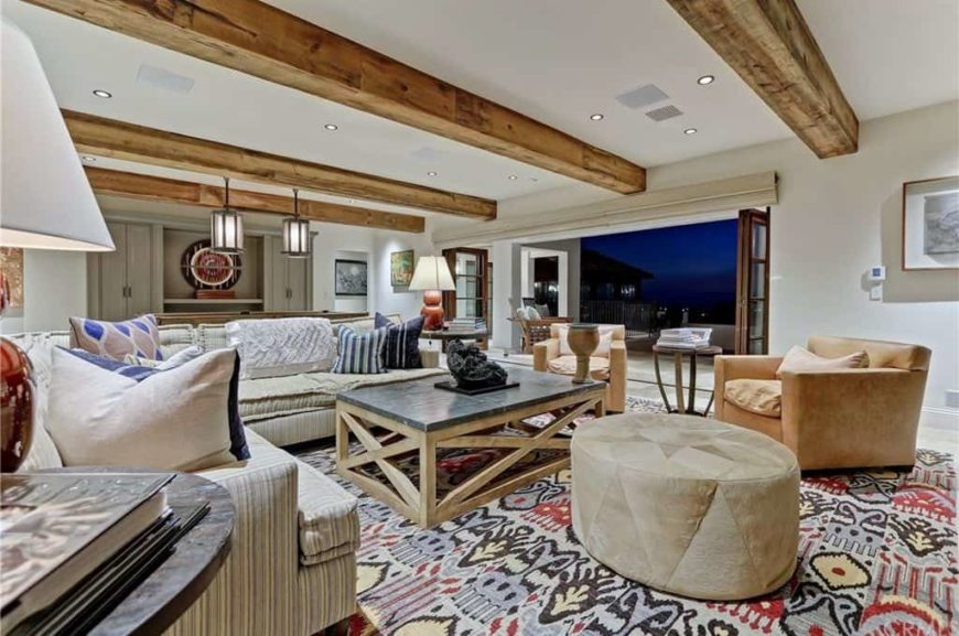 Large living space featuring a large area rug along with a ceiling with large exposed beams. The room offers classy chairs and a large L-shape sofa set lighted by table lamps.