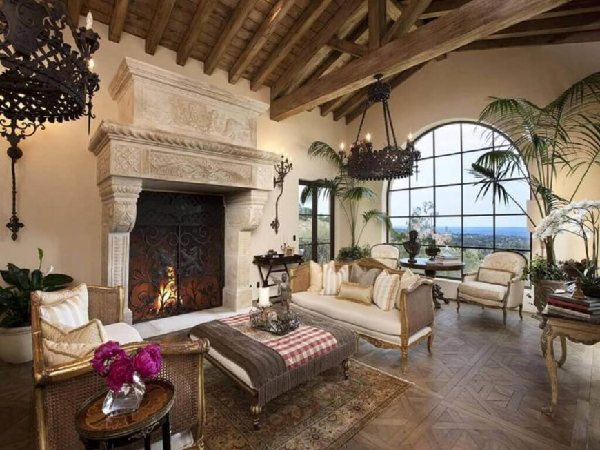 This home boasts a living space featuring a massive and elegant fireplace with classy couches set nearby. The area is lighted by fancy ceiling lights hanging from the high wooden vaulted ceiling with exposed beams.