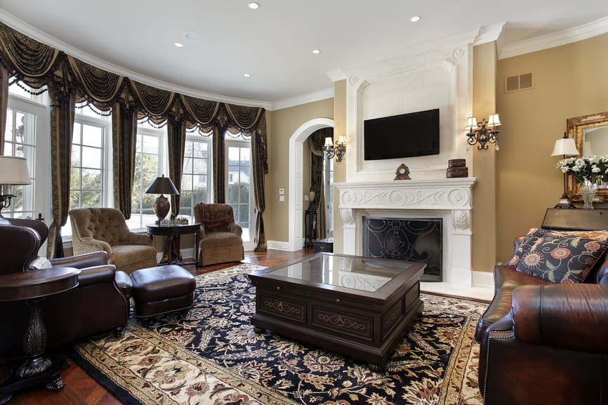 Large family living room with a set of elegant seats and window curtains, along with a classy white fireplace and a flat-screen TV above it. The room also has a stylish area rug covering the room's flooring.