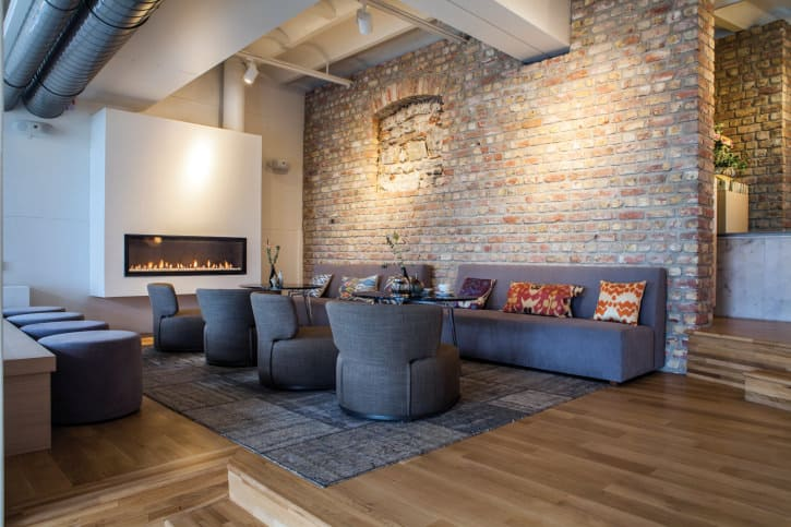 Large living room featuring a brick wall and hardwood floors. The area offers modern couches and chairs along with round tables and a gas fireplace.