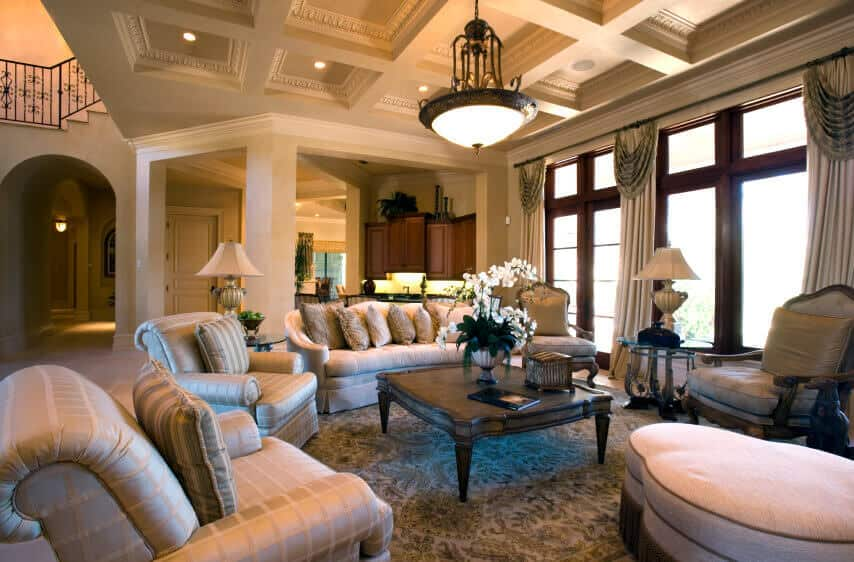 An elegant living space boasting a gorgeous coffered ceiling and luxurious pieces of furniture on top of the classy area rug covering the flooring.