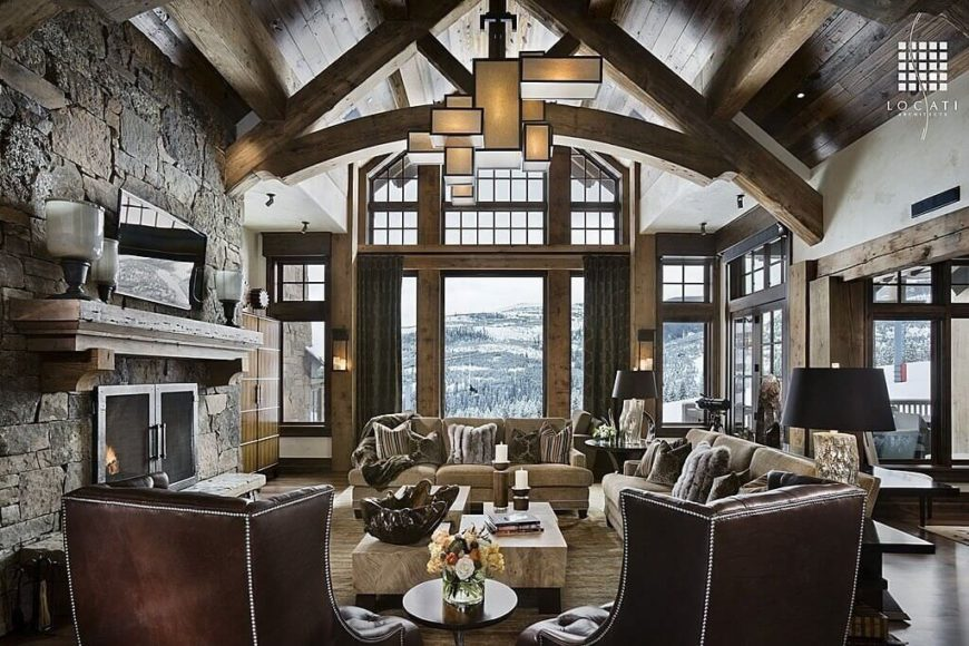Large living room under the home's tall wooden vaulted ceiling with large exposed beams. The area offers a large stone fireplace and a set of elegant seats lighted by a stylish ceiling light.