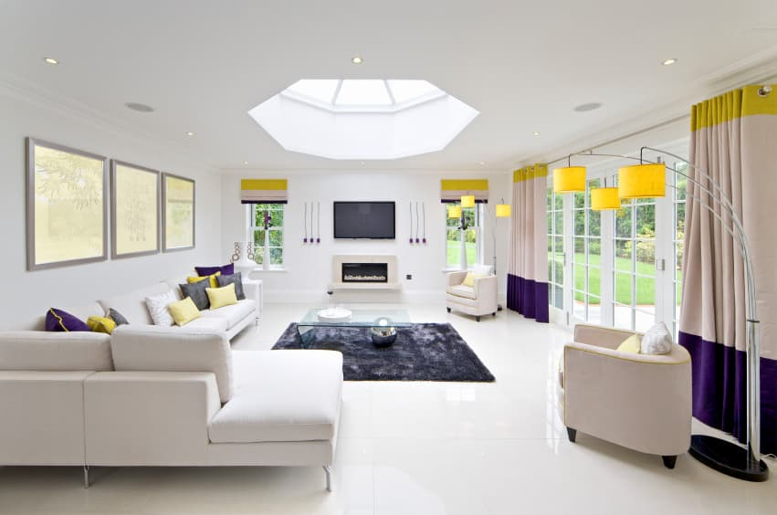 Spacious living room boasting white walls and a white ceiling with a skylight. The room also has a yellow and purple accent on its sofa set and window curtains.